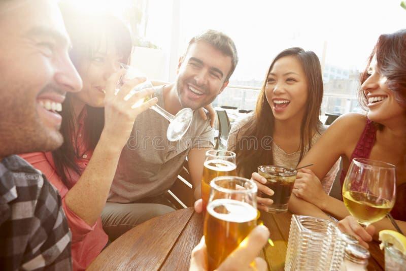 Grupo de amigos que disfrutan de la bebida en la barra al aire libre del tejado foto de archivo