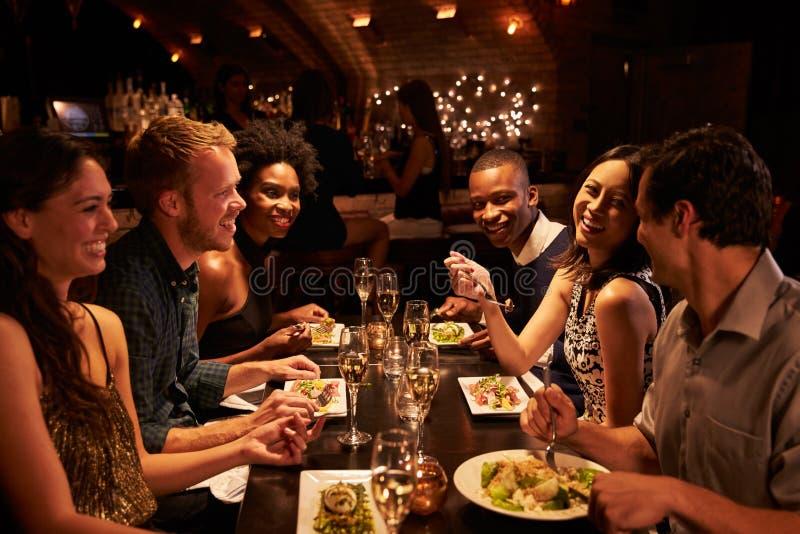 Grupo de amigos que disfrutan de la comida en restaurante imágenes de archivo libres de regalías