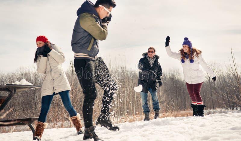 Grupo de amigos que disfrutan de una lucha de la bola de nieve en la nieve en invierno imágenes de archivo libres de regalías