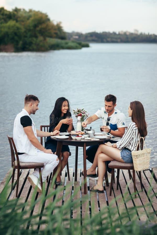 Grupo de amigos que disfrutan de la comida en comida campestre en embarcadero de la playa del río fotografía de archivo
