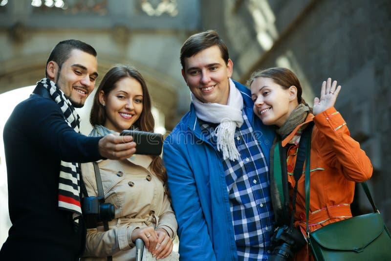 Grupo de amigos que disparam no retrato mútuo no telefone celular foto de stock royalty free
