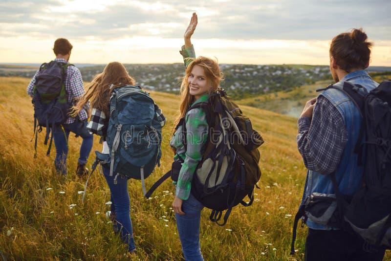 Grupo de amigos que emigran con las mochilas que camina en el bosque imágenes de archivo libres de regalías