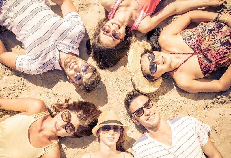 Grupo de amigos que encontram-se na praia imagem de stock royalty free