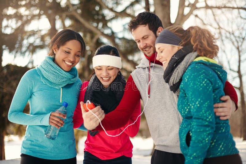 Grupo de amigos que escuchan la música en la nieve en invierno fotografía de archivo libre de regalías