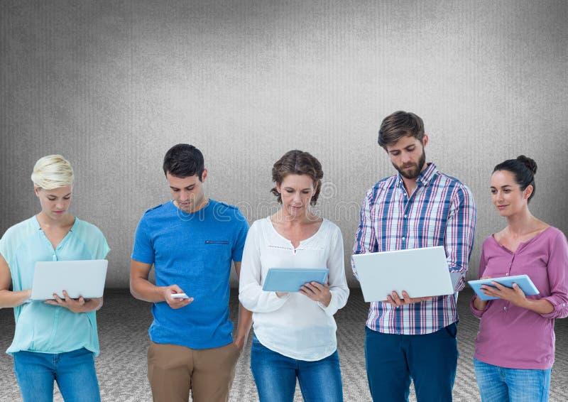 Grupo de amigos que estão na frente do fundo cinzento vazio com dispositivos fotografia de stock royalty free
