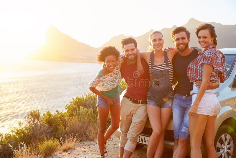 Grupo de amigos que estão pelo carro na estrada litoral no por do sol imagens de stock