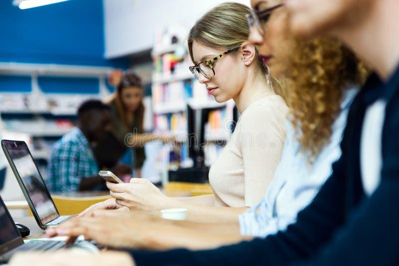Grupo de amigos que estudam em uma biblioteca da universidade foto de stock