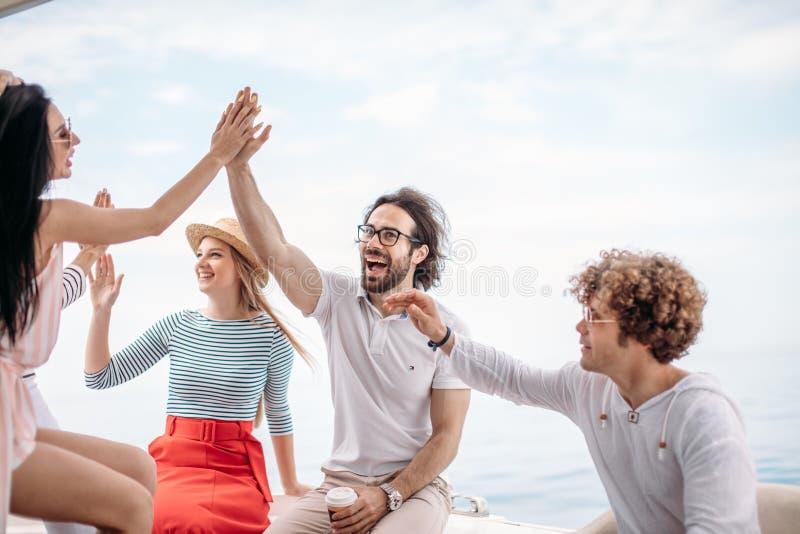 Grupo de amigos que fazem o partido em um iate, tendo um partido extravagante em um barco luxuoso imagens de stock royalty free