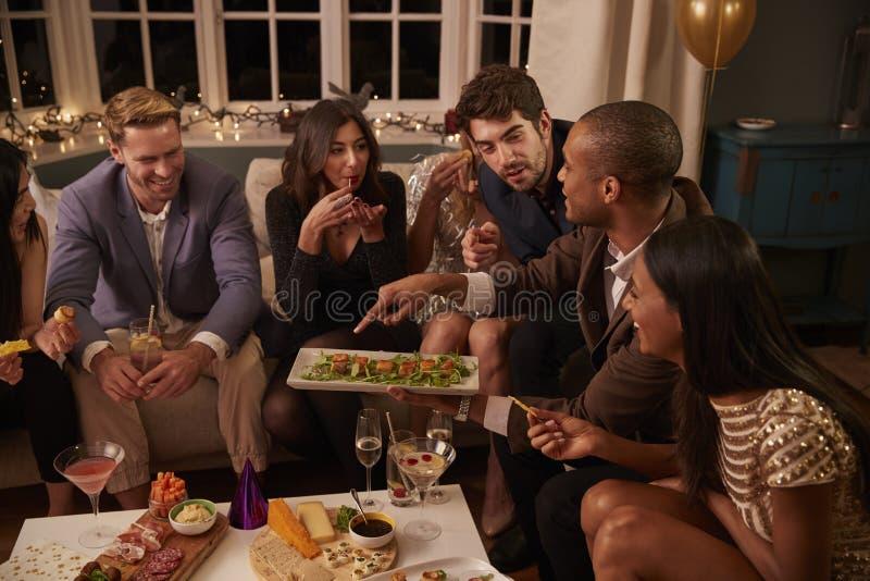Grupo de amigos que gozan de bebidas y de los bocados en el partido imágenes de archivo libres de regalías