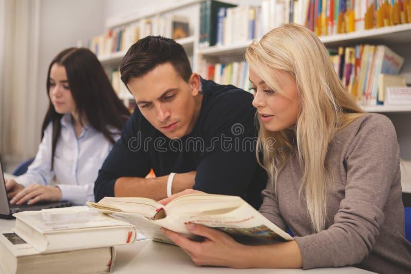 Grupo de amigos que gozan que estudia junto en la biblioteca imagenes de archivo