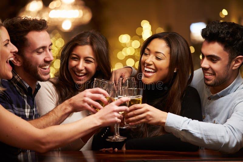 Grupo de amigos que gozan que iguala bebidas en barra imagenes de archivo
