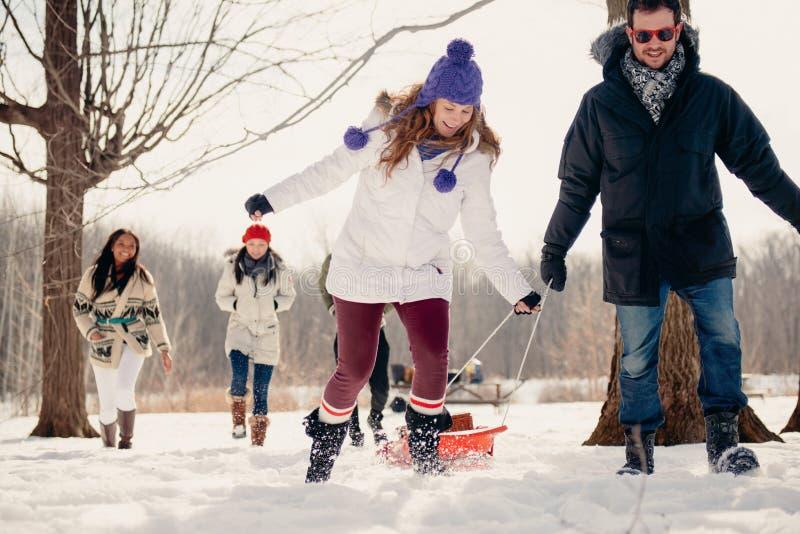 Grupo de amigos que gozan que tira de un trineo en la nieve en invierno imagenes de archivo