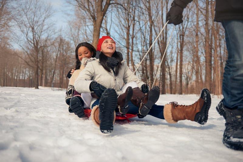 Grupo de amigos que gozan que tira de un trineo en la nieve en invierno fotos de archivo