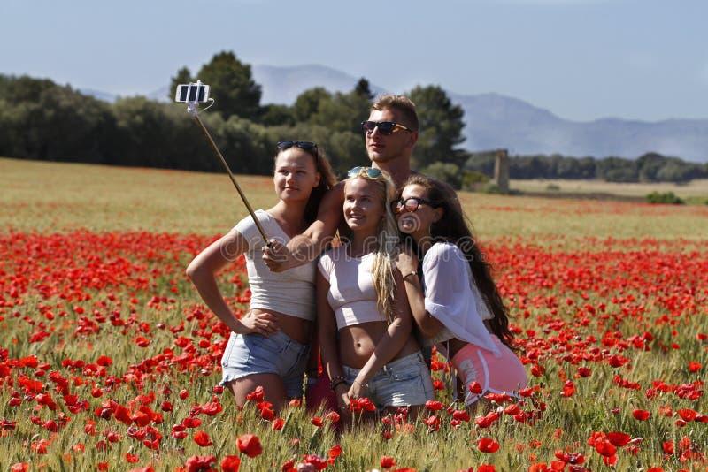 Grupo de amigos que hacen un selfie en un campo de amapolas fotos de archivo