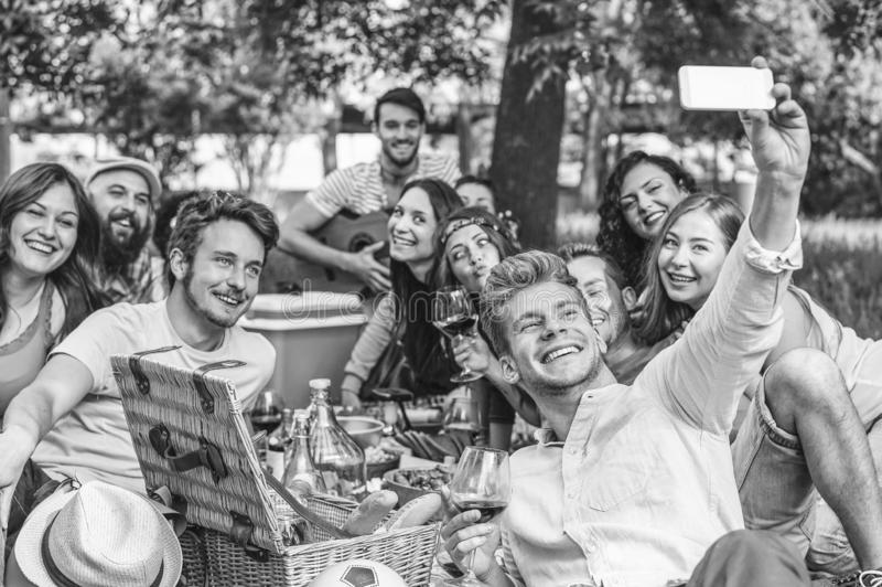Grupo de amigos que hacen una barbacoa de la comida campestre y que toman el selfie con smartphone m?vil en el parque al aire lib foto de archivo libre de regalías