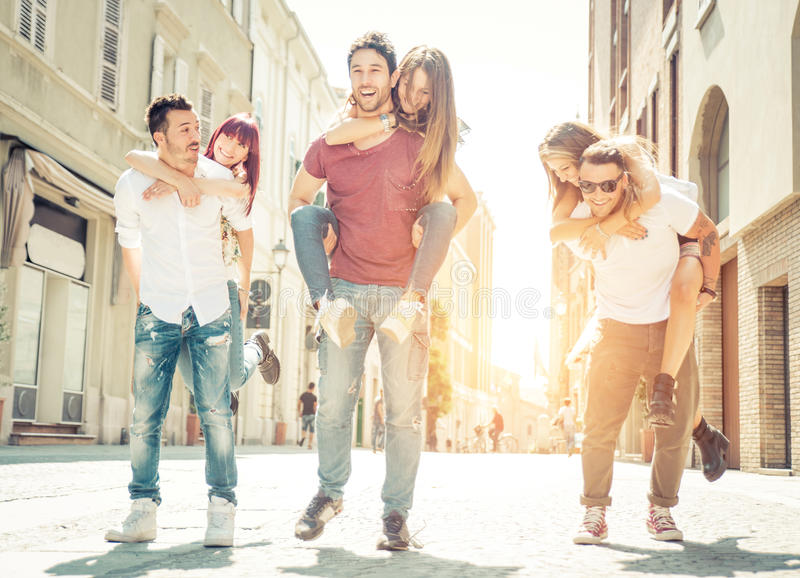 Grupo de amigos que juegan alrededor en el centro de ciudad foto de archivo
