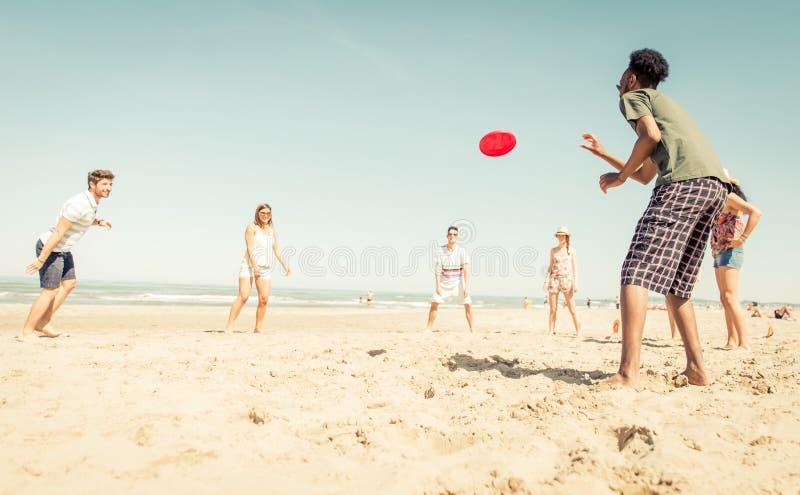 Grupo de amigos que juegan con el disco volador imagenes de archivo