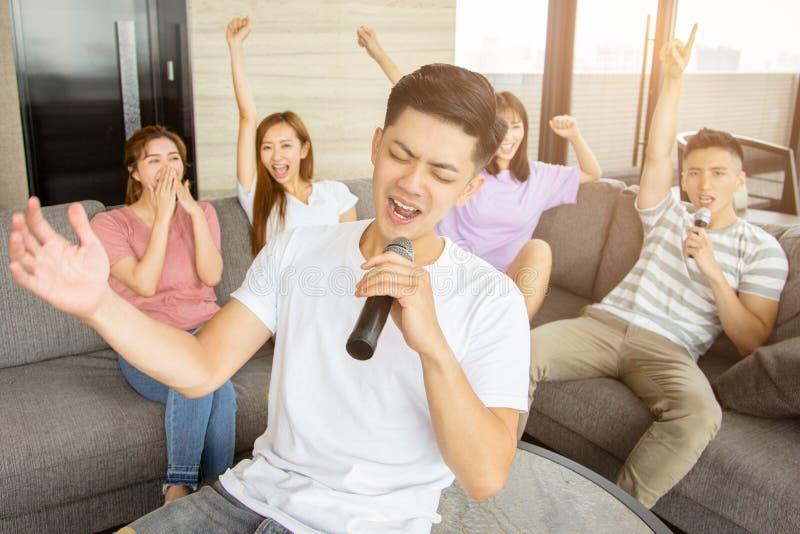 Grupo de amigos que juegan Karaoke en casa imagen de archivo