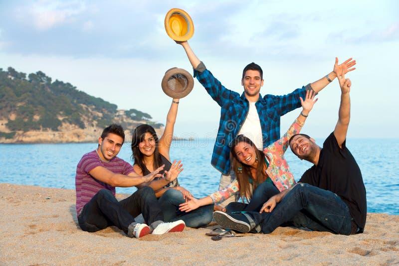 Grupo de amigos que levantan las manos en la playa. fotografía de archivo