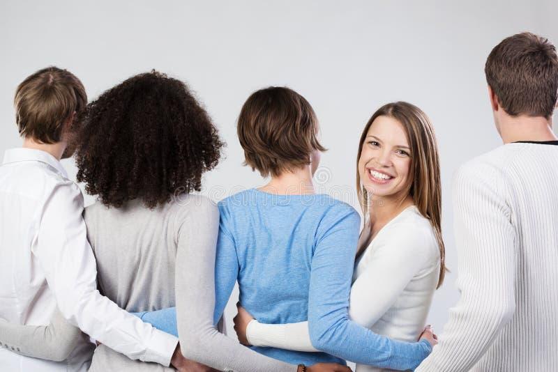 Grupo de amigos que ligan los brazos que hacen frente lejos imagen de archivo