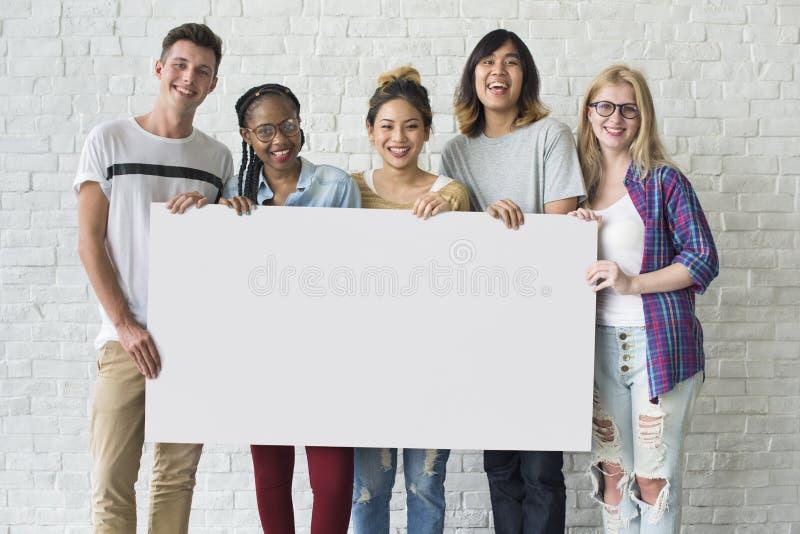 Grupo de amigos que llevan a cabo concepto en blanco de la bandera fotos de archivo libres de regalías