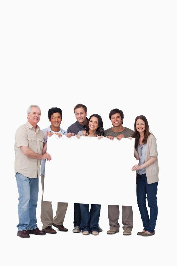 Grupo de amigos que mantêm o sinal em branco unido fotos de stock royalty free