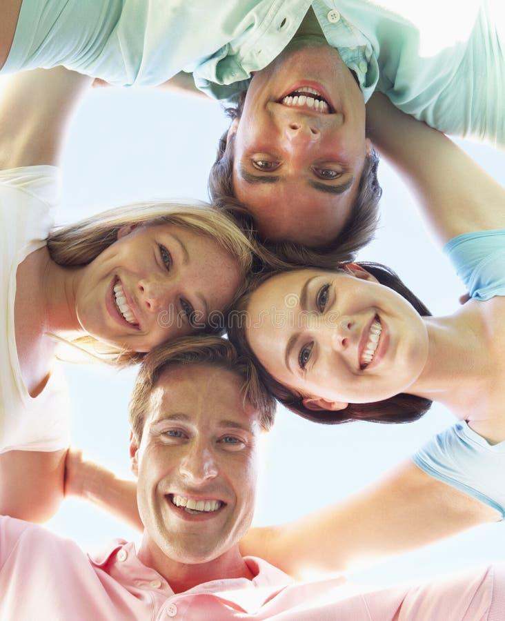 Grupo de amigos que miran abajo en cámara foto de archivo libre de regalías