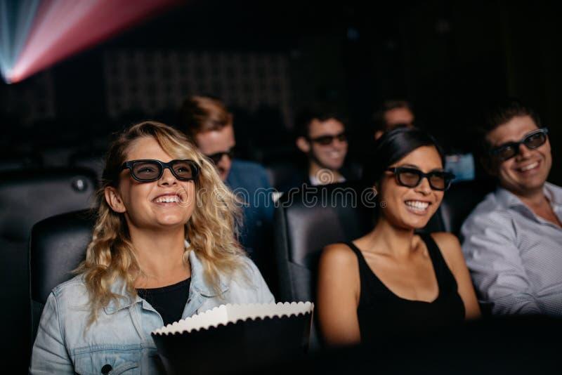 Grupo de amigos que miran la película 3d en cine fotos de archivo libres de regalías