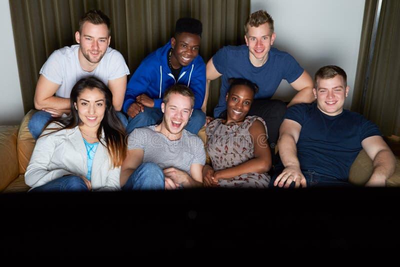 Grupo de amigos que miran la televisión en casa junto imagen de archivo