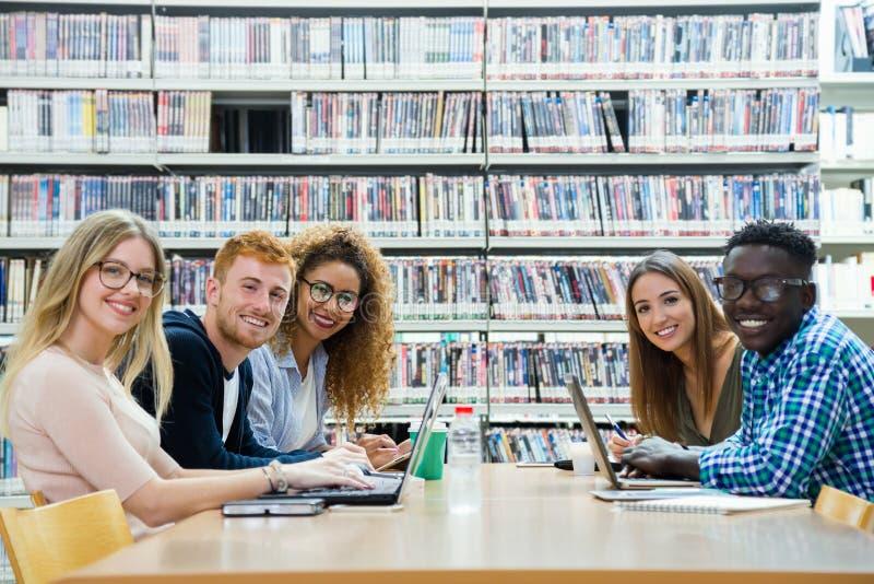 Grupo de amigos que olham a câmera em uma biblioteca da universidade imagem de stock royalty free