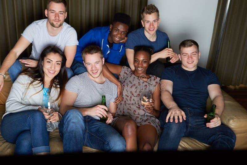 Grupo de amigos que olham a televisão em casa junto fotos de stock royalty free