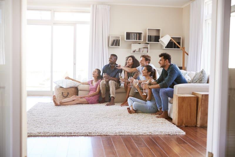 Grupo de amigos que relajan en casa la TV de observación junto fotos de archivo