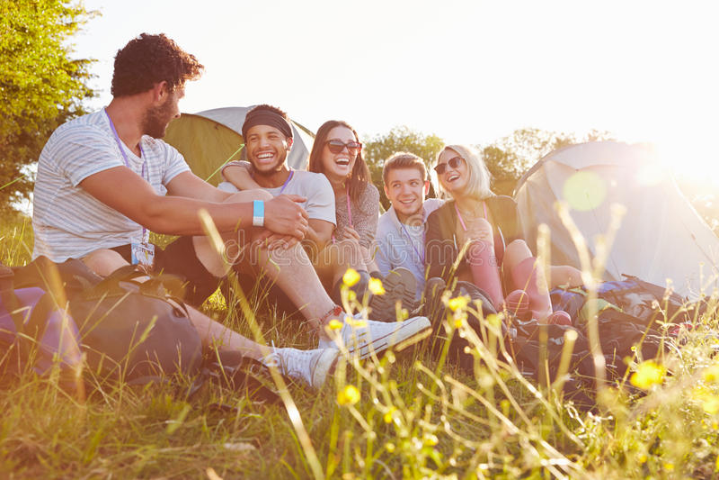 Grupo de amigos que relaxam fora das barracas no feriado de acampamento fotos de stock royalty free