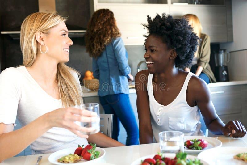 Grupo de amigos que riem ao comer o alimento saudável em casa imagem de stock