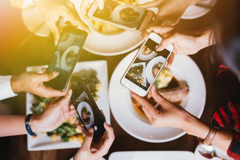 Grupo de amigos que salen y que toman una foto de la comida italiana así como el teléfono móvil foto de archivo