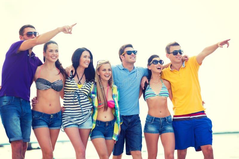 Grupo de amigos que señalan en alguna parte en la playa imagenes de archivo