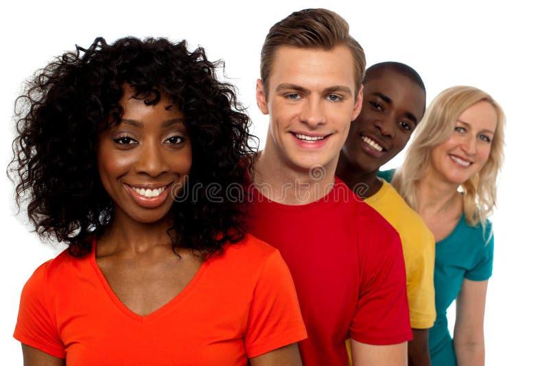 Grupo de amigos que se colocan detrás de uno otro imagen de archivo