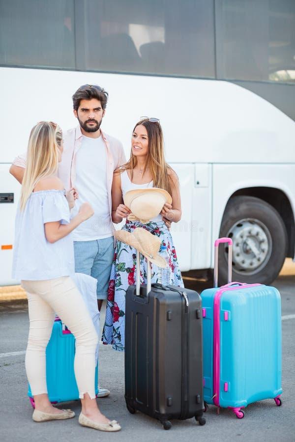 Grupo de amigos que se colocan en el término de autobuses y que esperan su autobús fotos de archivo libres de regalías
