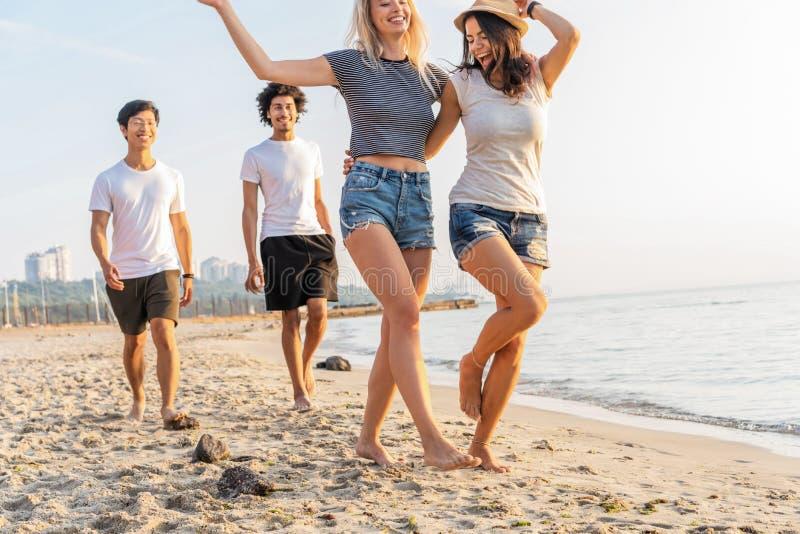 Grupo de amigos que se divierten que corre abajo de la playa en la puesta del sol fotografía de archivo