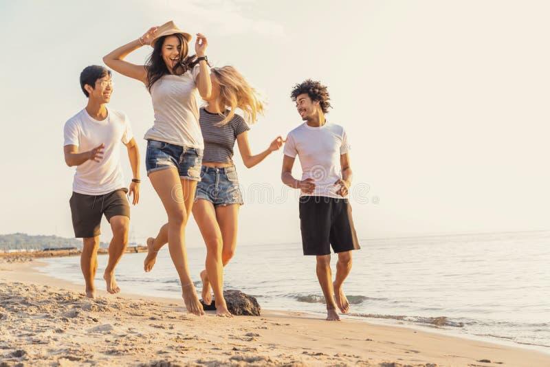 Grupo de amigos que se divierten que corre abajo de la playa en la puesta del sol fotografía de archivo libre de regalías