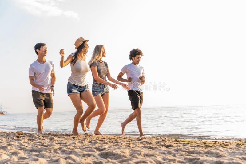 Grupo de amigos que se divierten que corre abajo de la playa en la puesta del sol imagen de archivo libre de regalías