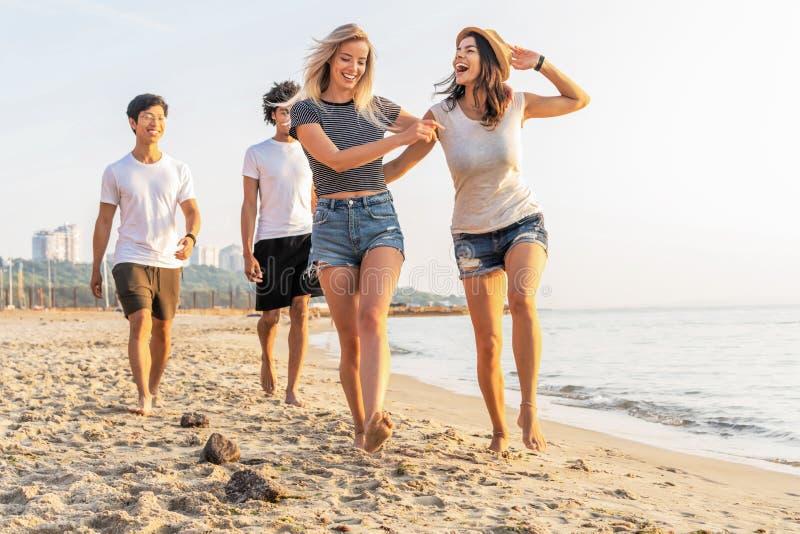 Grupo de amigos que se divierten que corre abajo de la playa en la puesta del sol imagen de archivo