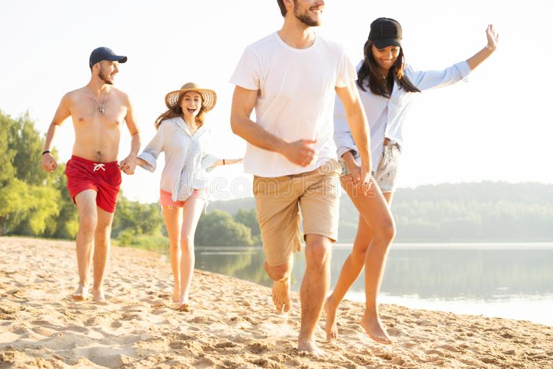 Grupo de amigos que se divierten que corre abajo de la playa imagenes de archivo