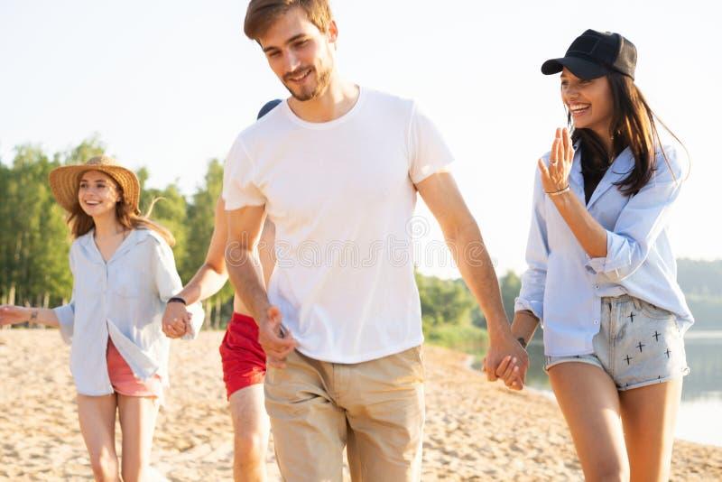 Grupo de amigos que se divierten que corre abajo de la playa fotos de archivo