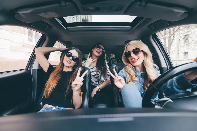 Grupo de amigos que se divierten en el coche Canto y risa en la impulsión del coche en centro de ciudad imagenes de archivo
