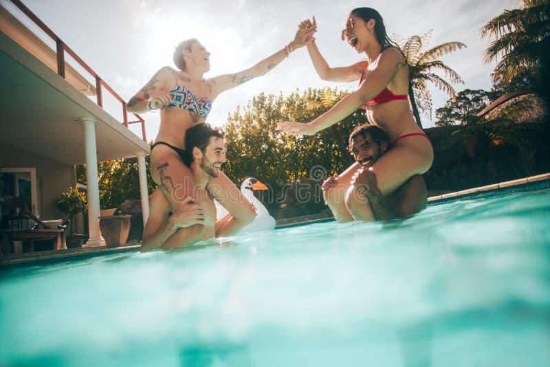 Grupo de amigos que se divierten en la piscina fotografía de archivo