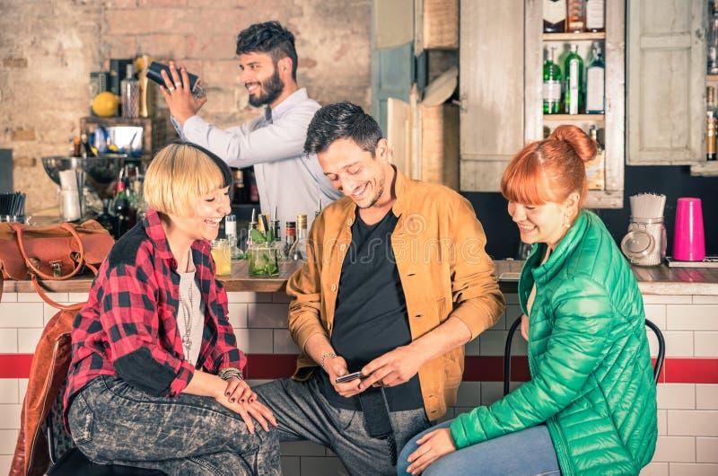 Grupo de amigos que se divierten usando smartphone en la barra del inconformista fotografía de archivo