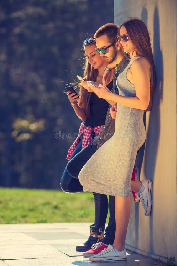 Grupo de amigos que se divierten y que usan sus teléfonos imágenes de archivo libres de regalías