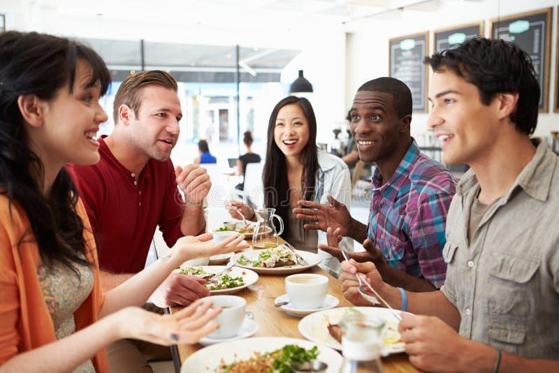 Grupo de amigos que se encuentran para el almuerzo en cafetería imagen de archivo
