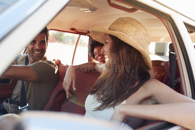 Grupo de amigos que se relajan en coche durante viaje por carretera imagen de archivo